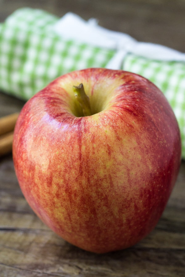 A large apple with a green & white checked hand towel and 2 cinnamon sticks in the background.