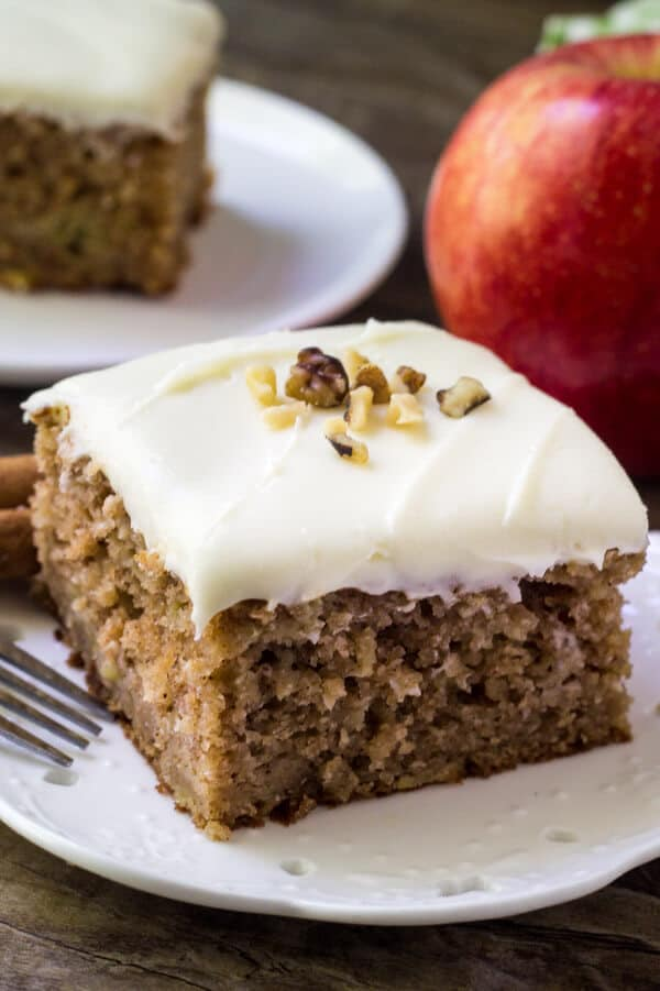 Slice of apple spice cake with cream cheese frosting topped with chopped walnuts. Apple and second slice of cake in the backround.