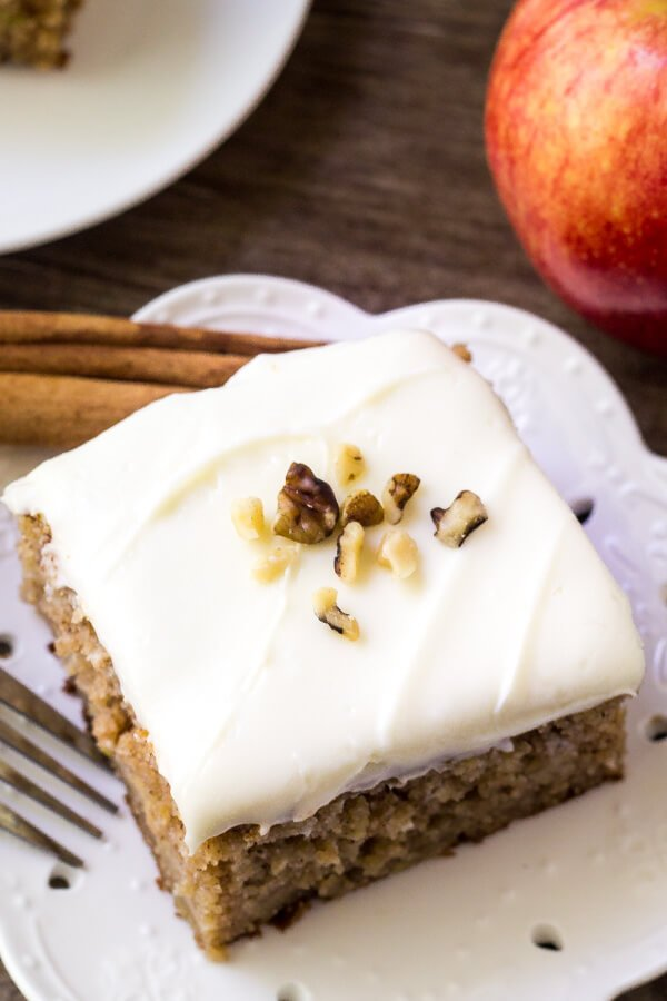 Overhead shot of a slice of apple spice cake with cream cheese frosting topped with chopped walnuts. Apple and second piece of cake in the background