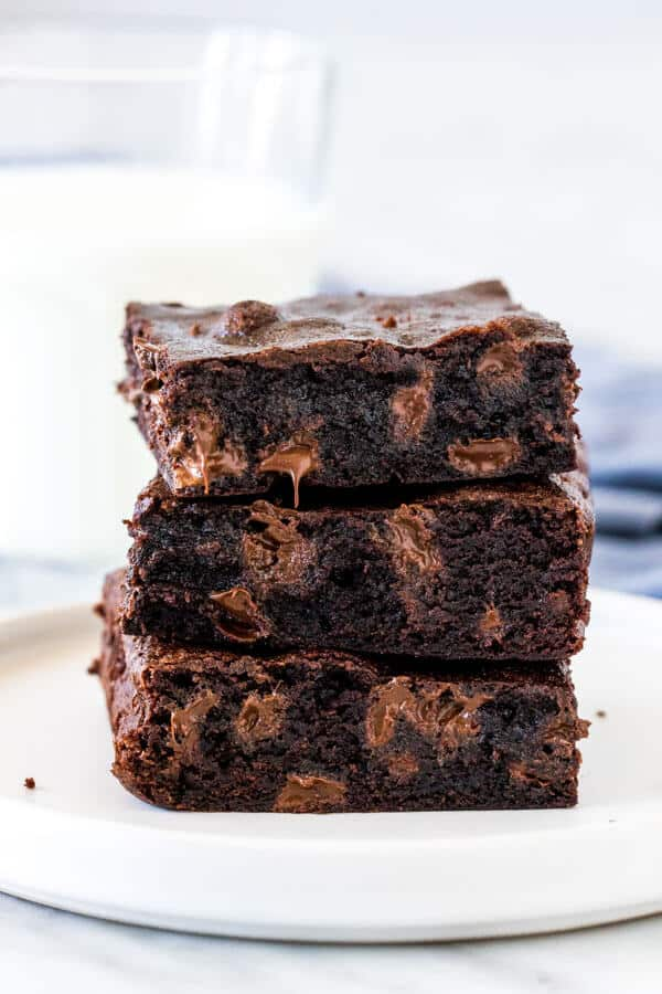 Stack of 3 chewy brownies with a glass of milk.