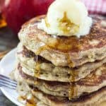 Stack of Apple Pancakes with Brown Sugar and Cinnamon. Topped with whipped butter and drizzled with maple syrup. Apple and bottle of syrup in background.