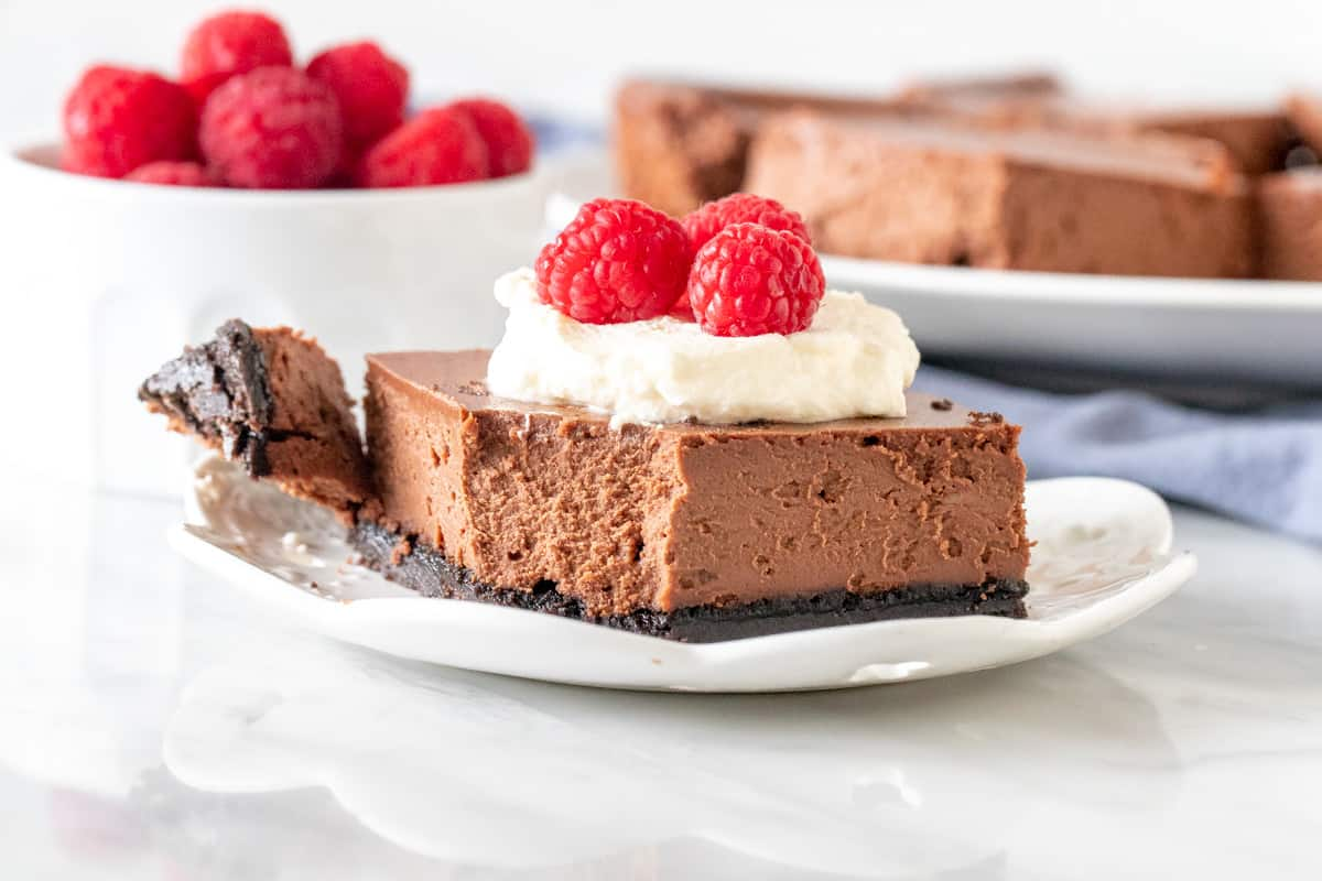 Chocolate cheesecake bar with cream and berries on top.