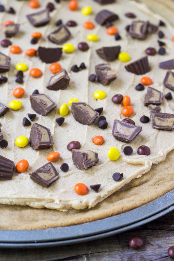Overhead shot of full peanut butter cookie pizza on it's pizza pan. With peanut butter frosting & peanut butter candies