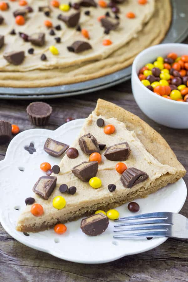 Slice of peanut butter cookie pizza topped with peanut butter frosting, peanut butter cups and peanut butter candies. Bowl of Reese's Pieces and whole cookie pizza in the background.