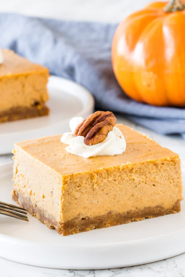 A slice of creamy pumpkin cheesecake bars taken from the side to show the creamy, smooth texture.
