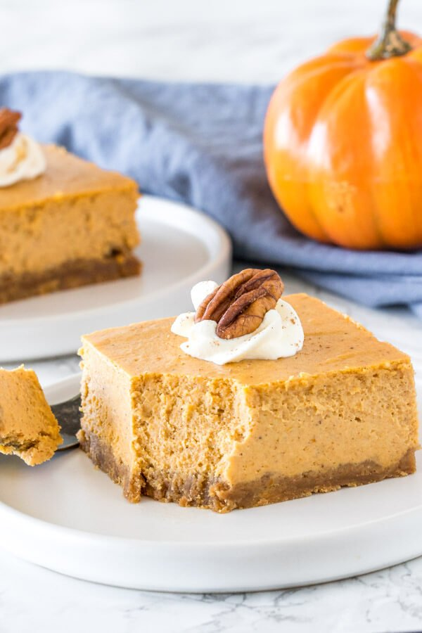 A slice of extra creamy pumpkin spice cheesecake with a bite taken out of it to show the texture.