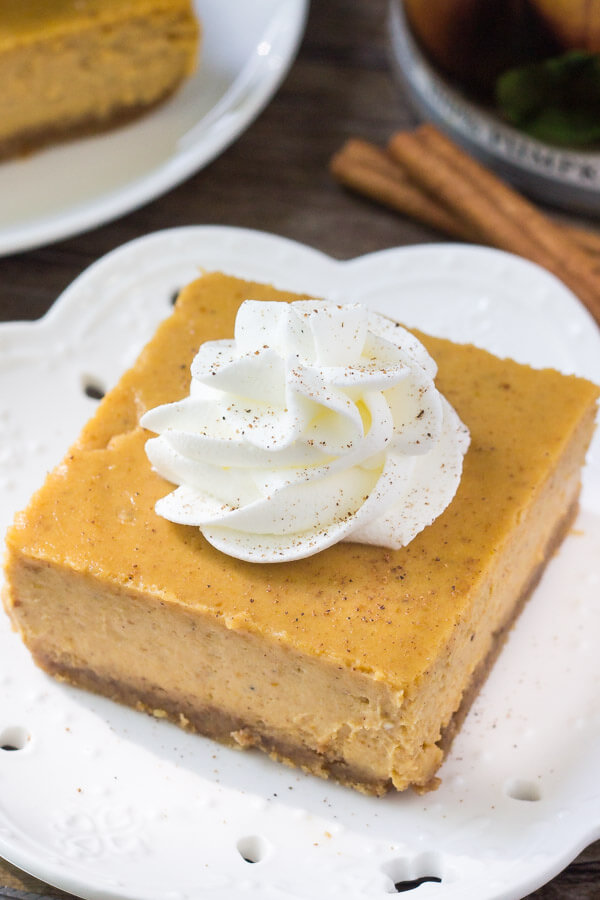 Overhead view of slice of pumpkin cheesecake topped with whipped cream.