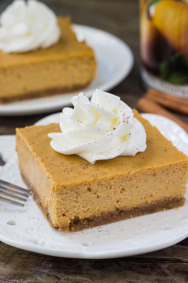 Side view of slice of pumpkin cheesecake squares on a white plate topped with whipped cream. Second piece of cheesecake and can of pumpkin puree in background.