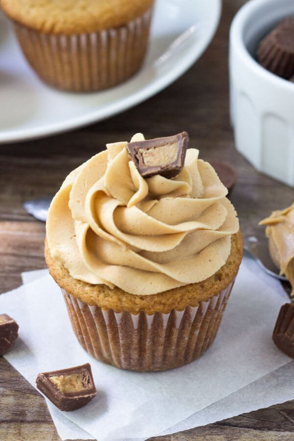Cupcake topped with creamy peanut butter frosting and a peanut butter cup. Glass of milk and plate of cupcakes in the background.