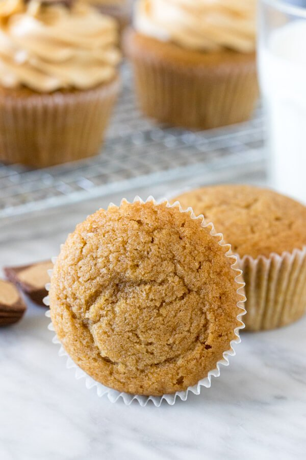Peanut butter cupcake on its side with a glass of milk and cooling rack of cupcakes.