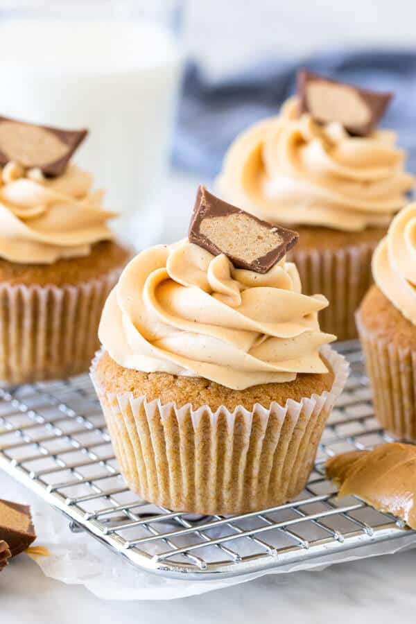 Peanut butter cupcakes on a cooling rack topped with a peanut butter cup.