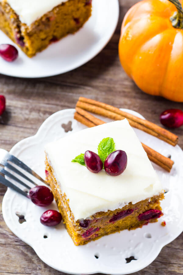 Overhead view of 2 slices of cranberry pumpkin cake with cream cheese frosting on white plates on a wooden table. Mini pumpkin in the background.
