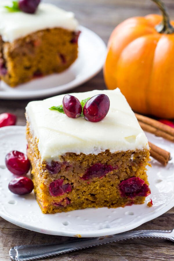 Side view of 2 slices of cranberry pumpkin cake with cream cheese frosting on white plates. Small pumpkin in the background.