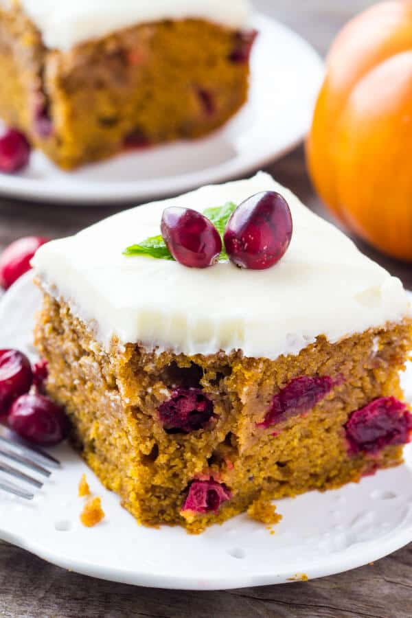 Slice of Cranberry Pumpkin Cake with Cream Cheese Frosting with a bite taken out of it and a fork resting on the side of the plate.