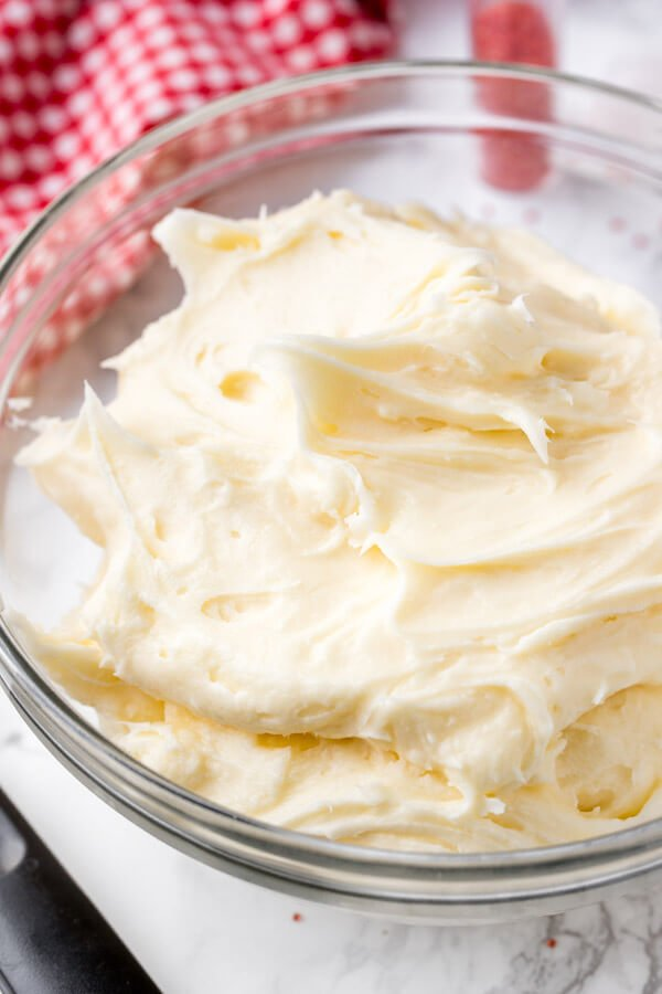 A bowl of cream cheese frosting for decorating red velvet cake.