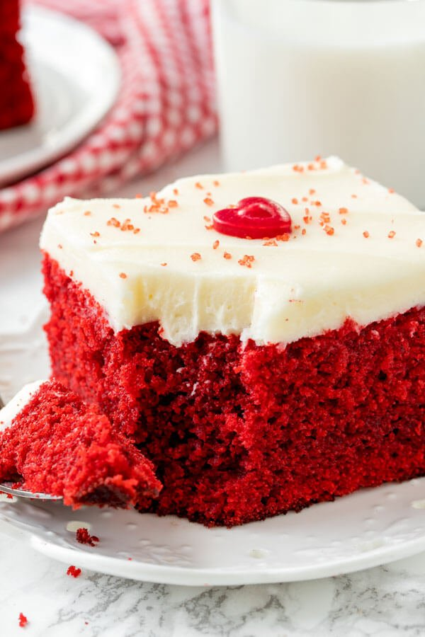 A slice of red velvet cake with cream cheese frosting on a white plate.