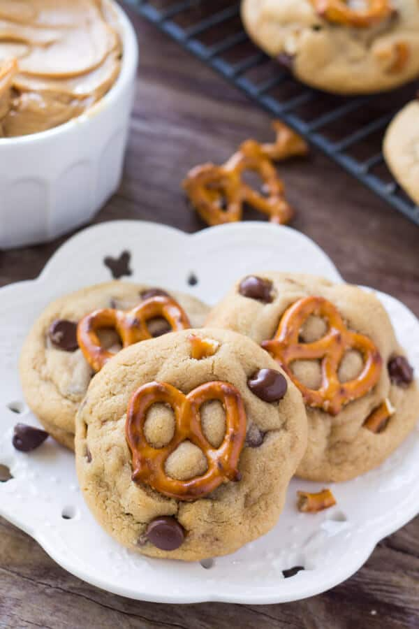 Three Peanut Butter Pretzel Cookies on a white plate with a small bowl of peanut butter and tray of cookies in the background.
