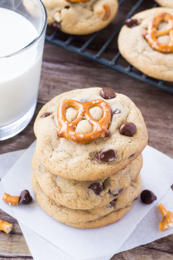 Stack of 3 peanut butter pretzel chocolate chip cookies with a glass of milk and cooling tray of cookies in the background.