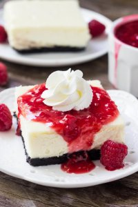 The absolute BEST white chocolate cheesecake bars with raspberry sauce. So creamy, not too sweet and with a delicious Oreo crust.