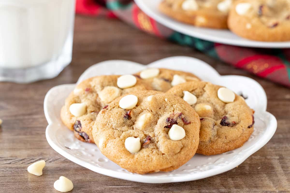 Plate of cranberry white chocolate cookies with a glass of milk.