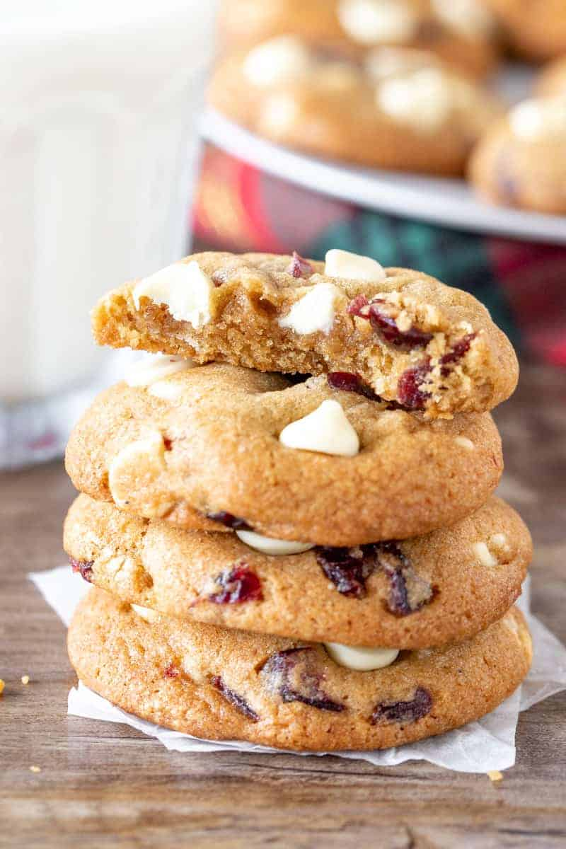 Stack of white chocolate cranberry cookies with the top cookie broken in half.