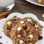 Three white chocolate cranberry oatmeal cookies on a white plate with a glass of milk and a second plate of cookies in the background.