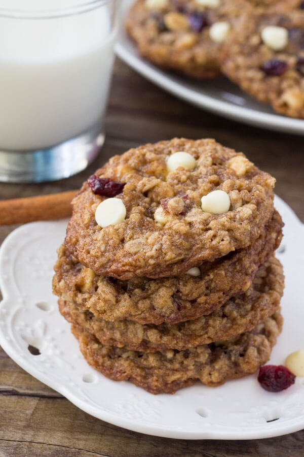 Stack of white chocolate cranberry oatmeal cookies on a white plate with a glass of milk and second plate of cookies in the background.