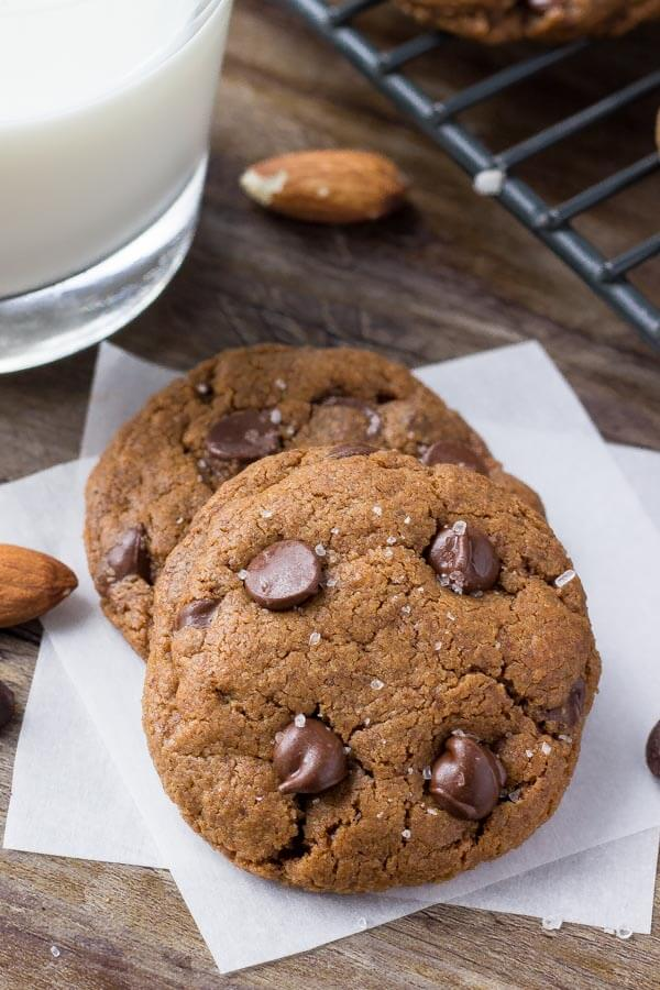 Two almond butter chocolate chip cookies with a glass of milk and wire rack of cookies cooling in the background.