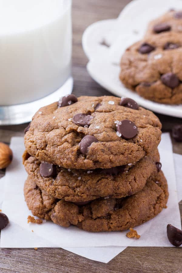 A stack of three gluten free almond butter cookies with dark chocolate chips.