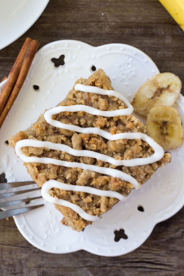 Overhead shot of a slice of banana coffee cake on a white plate with banana chips and cinnamon stick on the the plate.