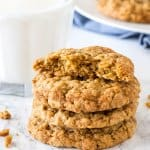 A stack of oatmeal cookies with the top cookie broken in half.