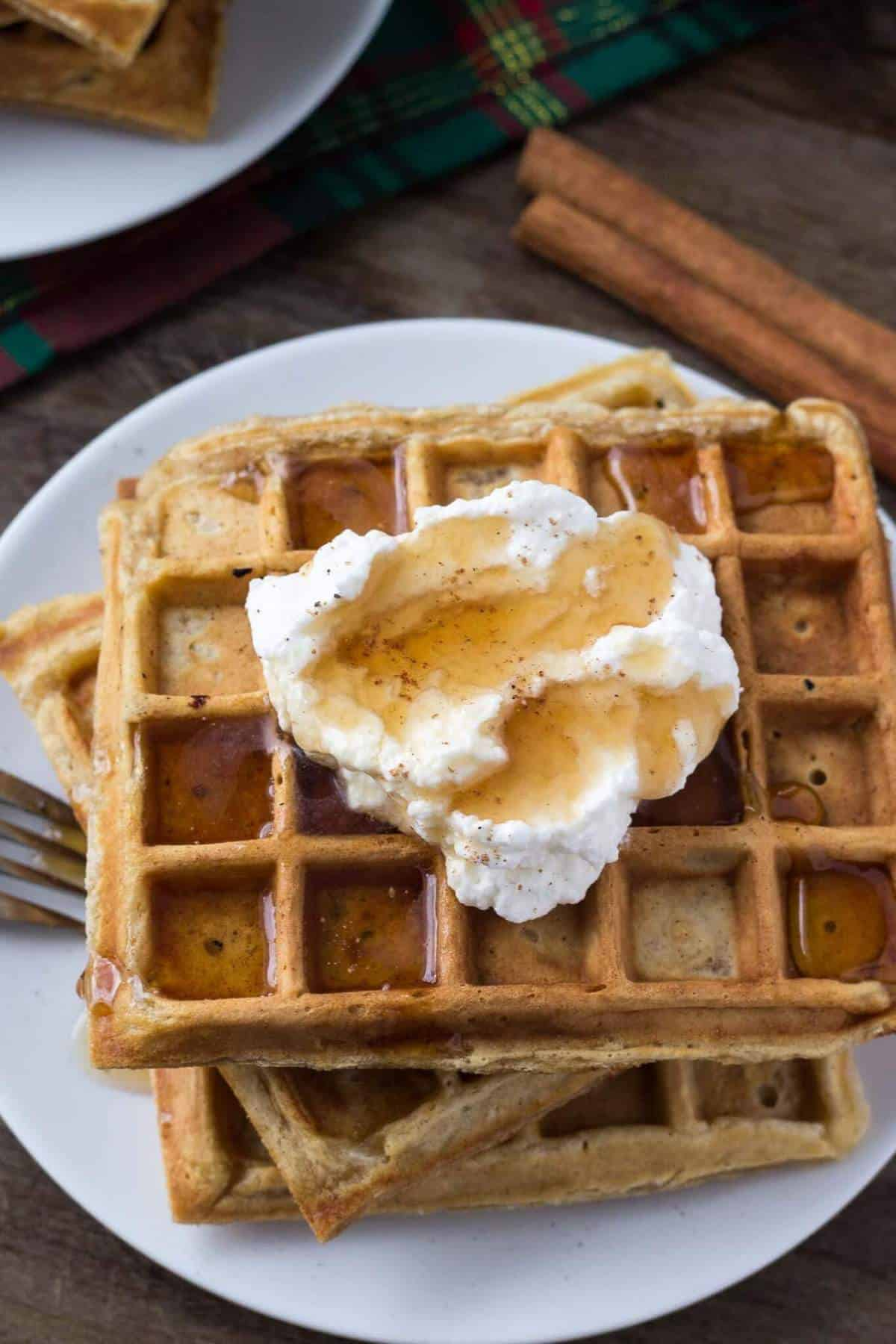 These fluffy eggnog waffles are the perfect breakfast for the holidays. They have soft centers, golden edges and a delicious hint of nutmeg.#eggnogwaffles