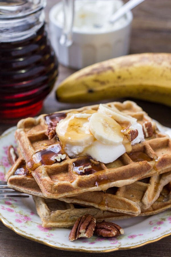 A stack of banana waffles drizzled with maple syrup and topped with whipped cream, chopped bananas & pecans.