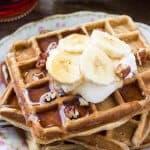 A stack of fluffy banana waffles taste like banana bread topped with maple syrup, whipped cream & sliced bananas.