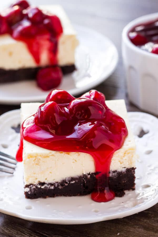 A slice of brownie cheesecake bars topped with cherry pie filling. They have a fudgy brownie bottom and a layer of creamy cheesecake on top.