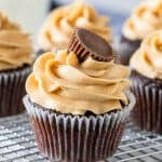 Chocolate cupcakes with peanut butter frosting on a wire rack.