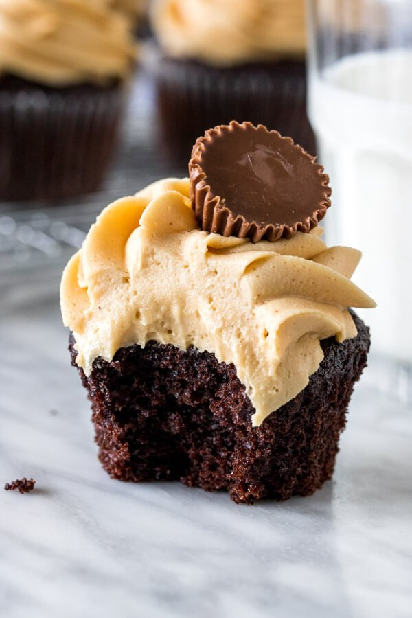 Chocolate cupcake with a bite taken out of it beside a glass of milk.