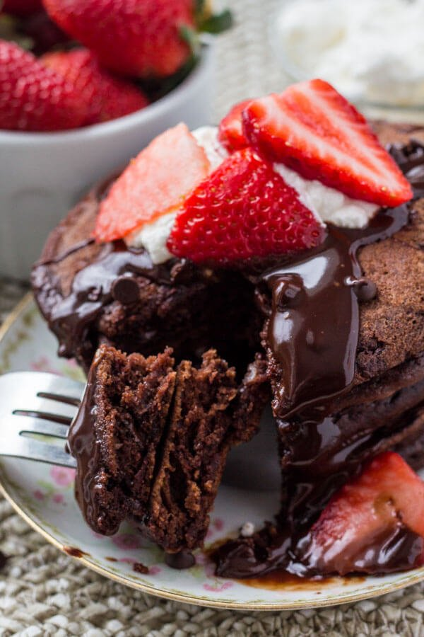 A stack of fluffy chocolate pancakes drizzled with chocolate ganache