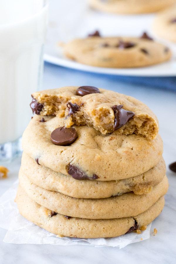 Stack of soft chocolate chip cookies. Top cookie broken in half.