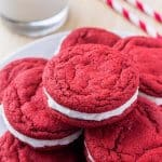 A plate of red velvet sandwich cookies with cream cheese frosting and a glass of milk.