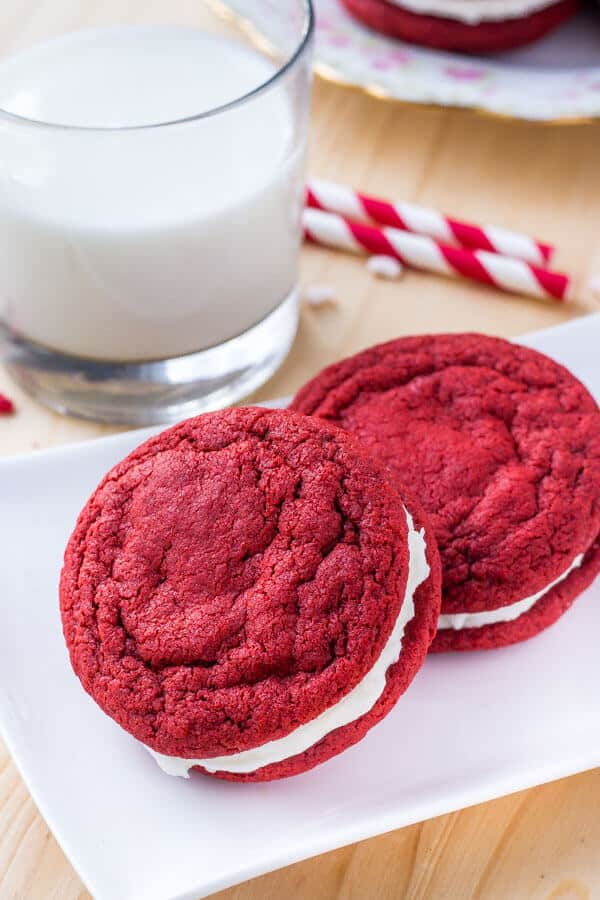 Two homemade red velvet sandwich cookies with cream cheese frosting.