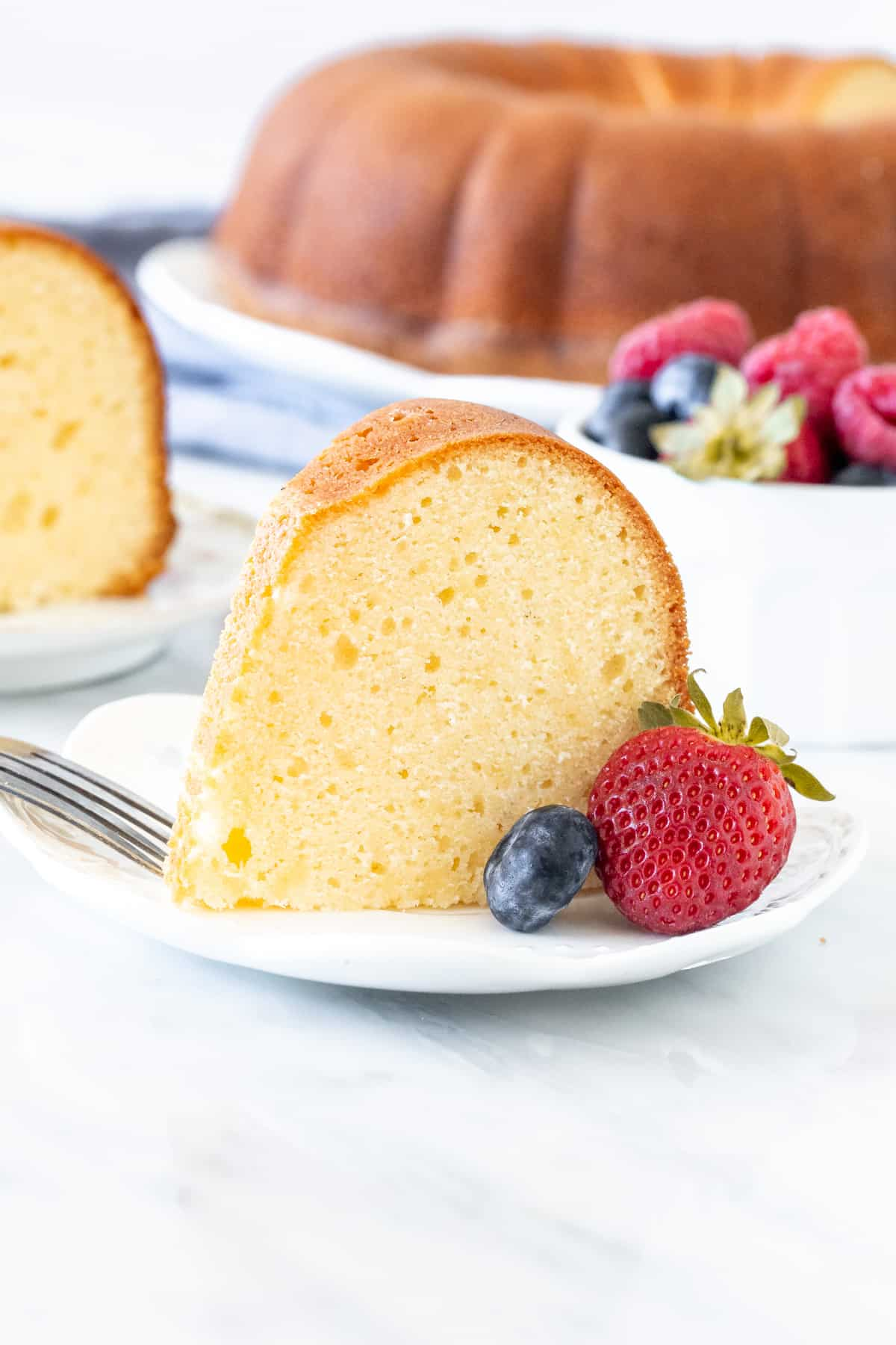 Slice of moist pound cake with berries on a plate.
