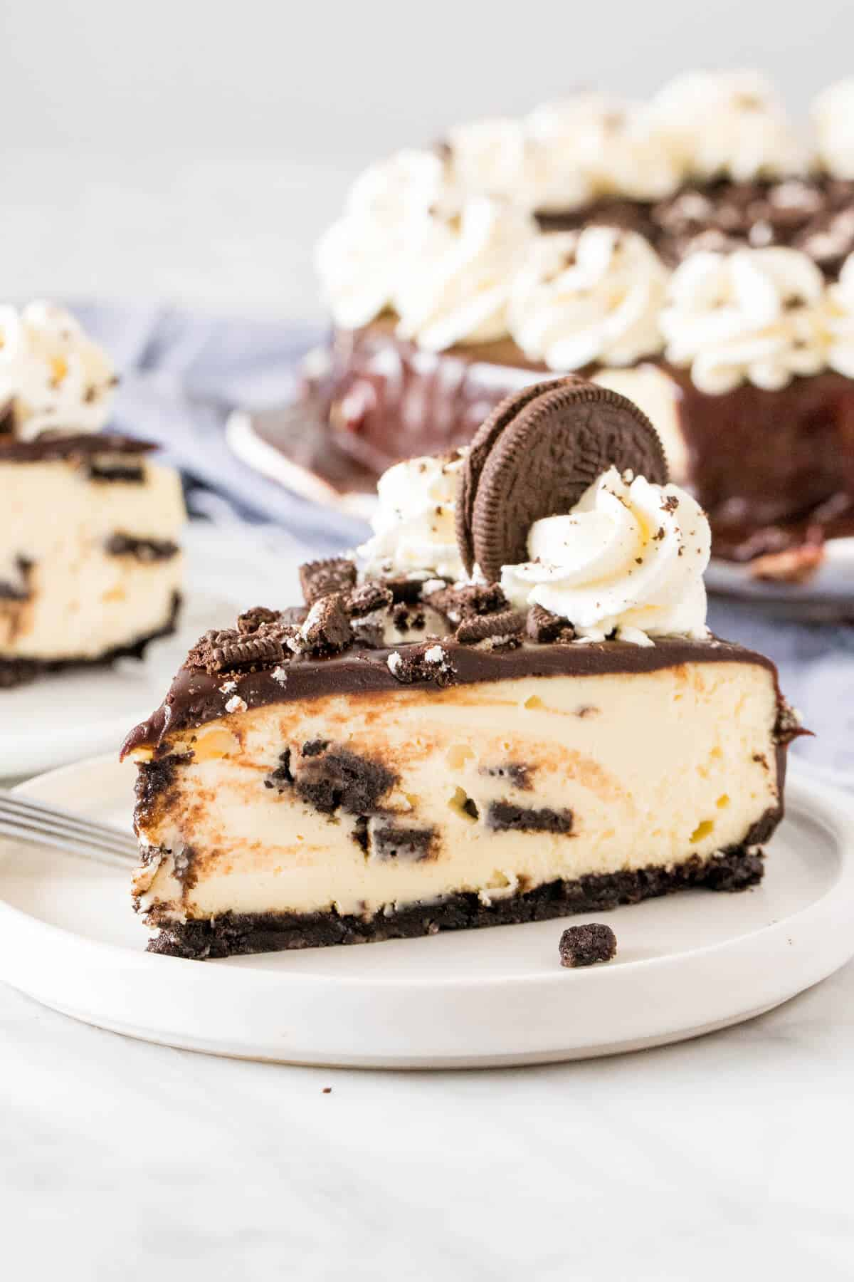 Slice of Oreo cheesecake with chocolate ganache and crushed Oreos on top.