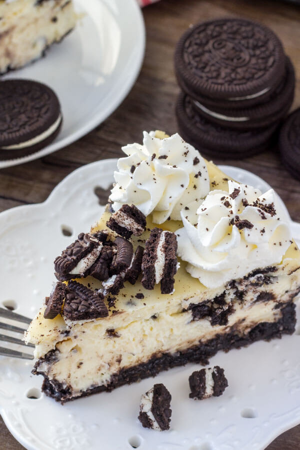 Smooth and creamy Oreo Cheesecake with an Oreo cookie crushed, Oreo pieces and topped with whipped cream.