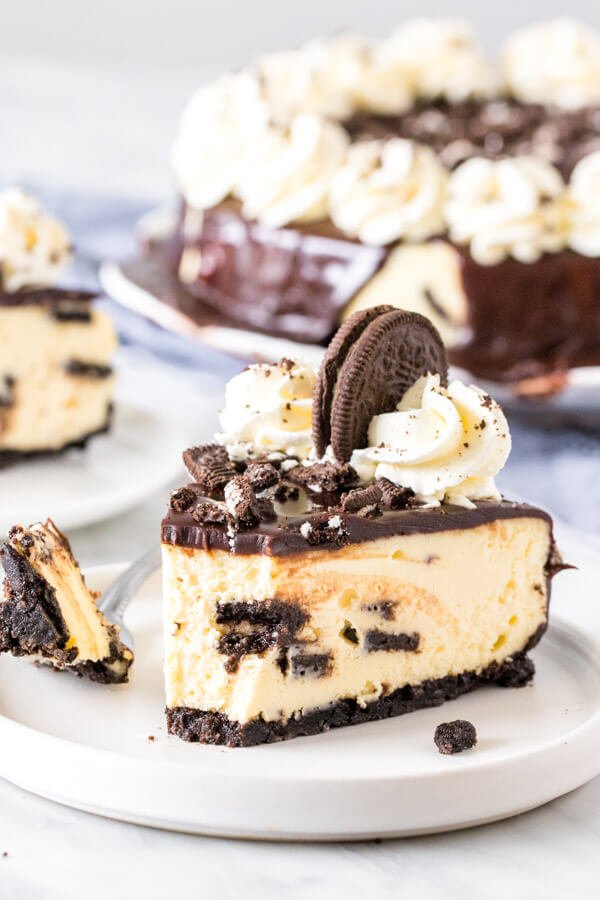Slice of cookies and cream cheesecake with a bite taken out of it.