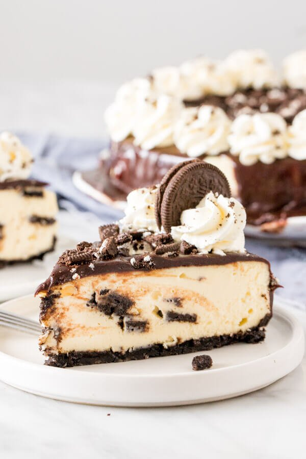Slice of Oreo cheesecake on a plate, with a 2nd slice in the background.