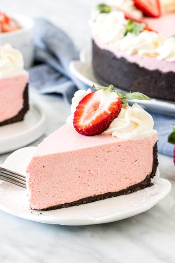 Slice of strawberry cheesecake with Oreo crust.