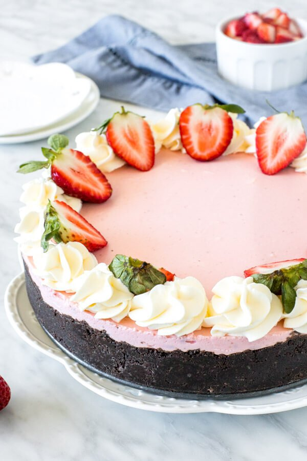 Strawberry cheesecake decorated with whipped cream and strawberry halves around the edges.
