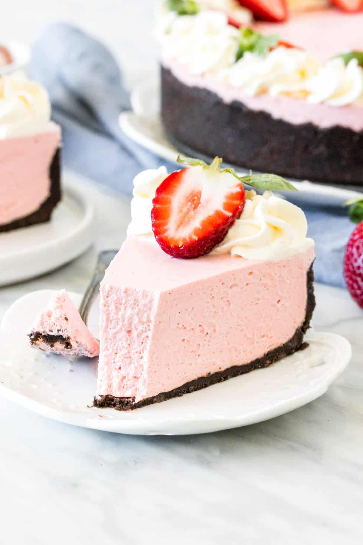 A slice of no-bake strawberry cheesecake with Oreo crust.