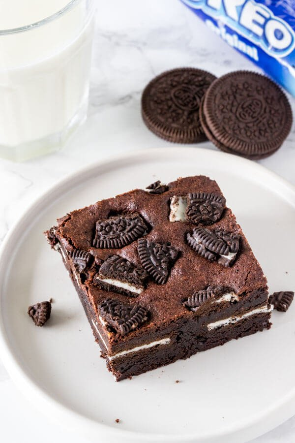 A chewy oreo stuffed brownie with chopped oreos on top with a glass of milk.